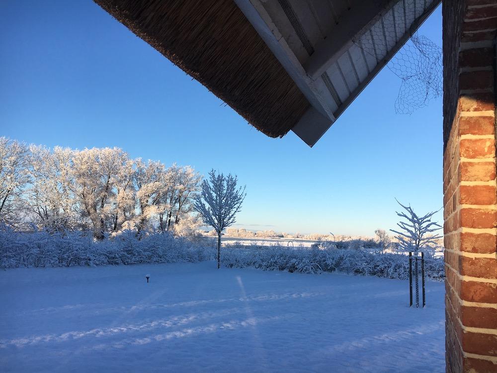 Blick aus dem Reethaus in den schneebedeckten Garten